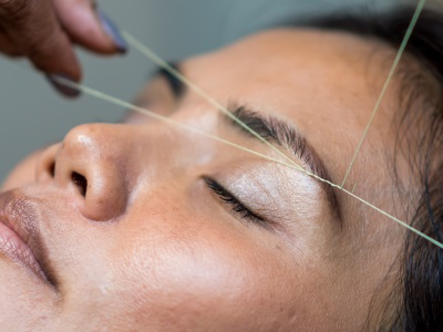 A person's eyebrows being threaded