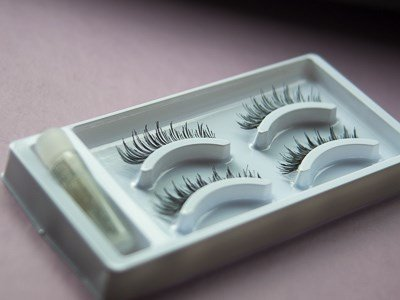 A tray containing strips of false eyelashes and glue