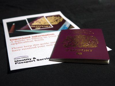 A red UK passport sat onto top the Identities and Passport Services information leaflet.